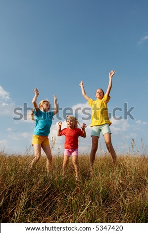 Girls wearing colorful t-shirts playing on a meadow - stock photo