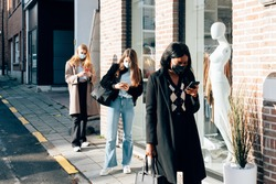 girls wearing face mask using a mobile phone while waiting on the street the opening of fashion retail during the black friday discount. Social distancing and new normal concept.