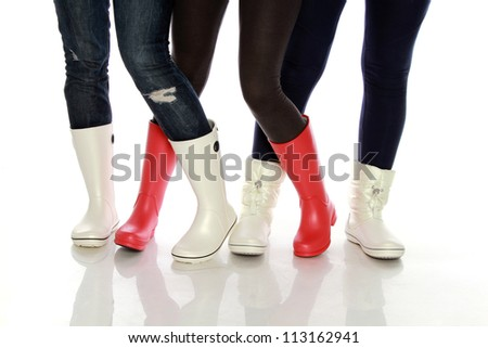 Girls wearing rubber shoes on white background - stock photo