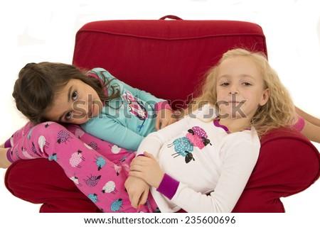 Girls wearing winter pajamas sitting red chair