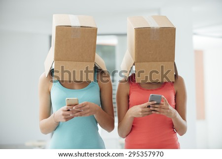 Girls with a box on their heads texting with a smart phone, social isolation and lack of communication concept