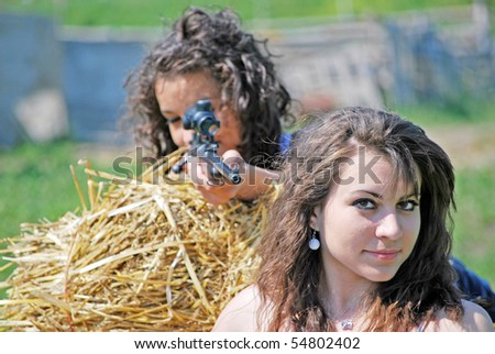 girls with gun on a hay bale
