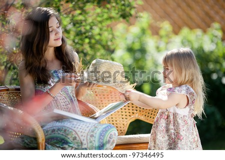 Girls with hat sitting in wicker chairs outdoor in summer day