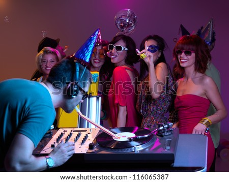 girls with paty hats and party horns, laughing and dancing, with dj mixing and playig with party horn