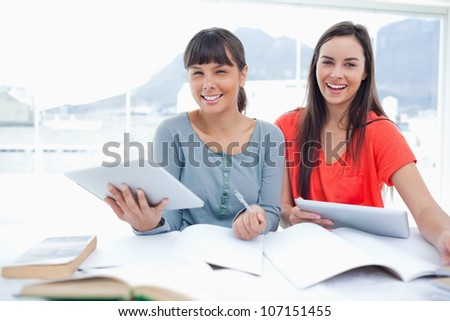 Girls working together with their tablet pc's in hand as they both look at the camera