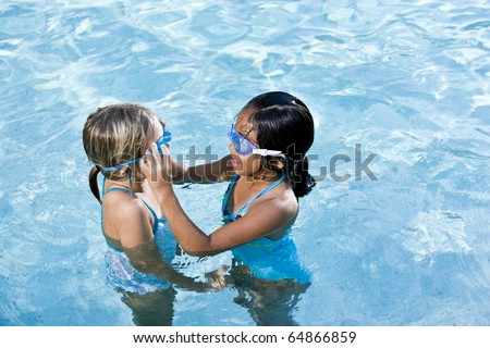 Girls, 7 years, adjusting swim goggles in swimming pool