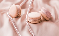 Girly, bakery and branding concept - Sweet macaroons and pearls jewellery on silk background, parisian chic jewelry, French dessert food and cake macaron for luxury confectionery brand, holiday gift