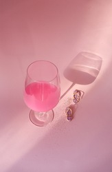 Girly pink conceptual photo of summer holidays with pink beach slippers and transparent wine glass with pink drink on a pink background with shadows of wine glass.