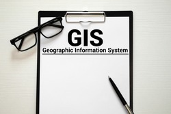 GIS - Geographic Information System write on a book isolated on Wooden Table