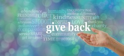 GIVE BACK word tag cloud - female open hand gesturing towards the words GIVE BACK surrounded by a relevant word cloud against a blue bokeh background