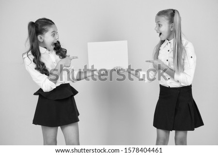 Give it publicity. Small kids pointing fingers at blank poster for school publicity. Little children showing publicity event on empty paper sheet. Publicity agents, copy space.
