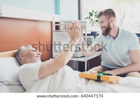 Give me five! Young stylish red bearded guy is visiting and cheering up his grandpa lying in bed at the modern hospital ward #640447174