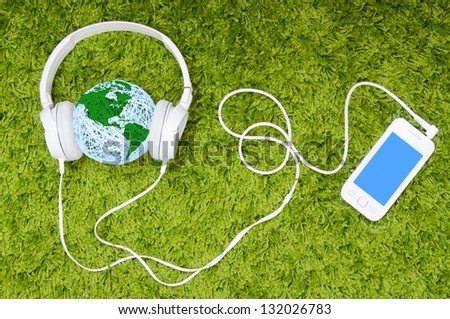 Give peace a music! White headphones and ball made of thread with map on it, on the green carpet.