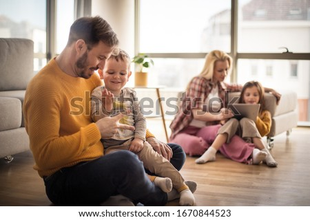 Give them a childhood to smile about. Family at home. Focus on foreground. Stockfoto ©