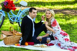 Give uncommon, unique gifts spontaneously. Enjoying their perfect date. Couple in love picnic date. Spring weekend. Happy loving couple relaxing in park with food. Romantic picnic with wine.