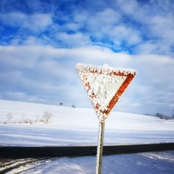 give way road sign, traffic sign, yield sign, with blue sky and clouds and with snow in winter season