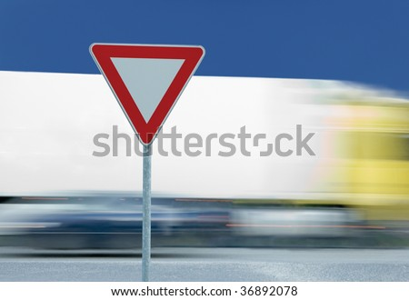 Give way yield road traffic sign, truck in the background