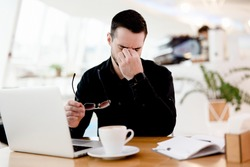 Give your eyes a rest Young tired freelancer man in black shirt suffers from pain and dryness in the eyes. He works a lot Cozy coffeehouse atmosphere on background. Cup of yummy cappuccino on table.