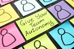Give Your Team Autonomy sign and drawn smiles faces.