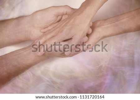 Giving a gentle blessing - cupped male hands being held and blessed by female hands on a wispy smoke effect background and copy space below  #1131720164