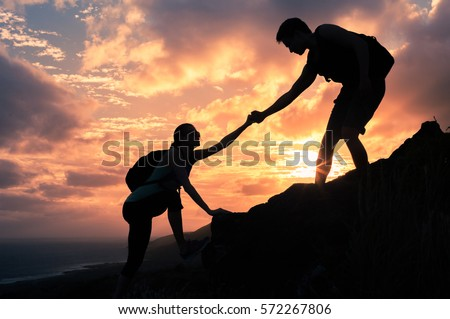 Giving a helping hand. Man helping female climber up a mountain.