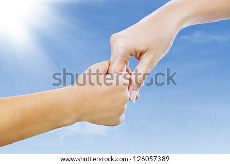 Giving a helping hand. Picture of a mother and son holding hands under blue sky.