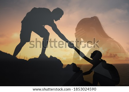 Giving a helping hand to someone in need. Sad depressed woman in the darkness being helped up and rescued by friend.  Foto stock ©