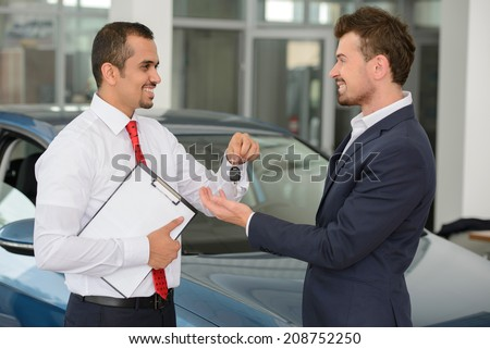 Giving a key of a brand new car. Handsome young classic car salesman giving a car key to the owner and smiling