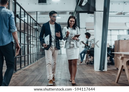 Giving business advice. Full length of two young colleagues in smart casual wear discussing business while walking through the office corridor