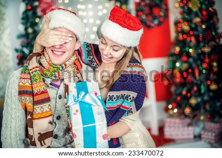 Giving gifts at Christmas. Loving couple give gifts at Christmas. Young couple in love man and pretty girl wearing sweater and scarf at home