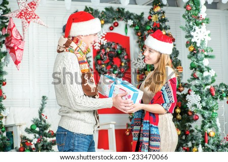 Giving gifts at Christmas! Young handsome guy gives gifts to his girlfriend. Loving couple wearing warm sweater and scarf in Christmas decorated room.