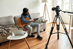Giving guitar online lesson. Young man blogger or music teacher sitting on sofa with a guitar, recording video tutorial at home. Focus on a man. Stay home, quarantine. E-learning. Online education