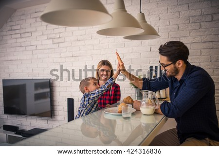 Giving high five to daddy while eating in the kitchen.