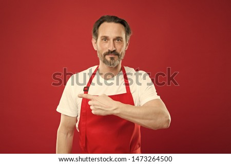 Giving instructions. Cook with beard and mustache wear apron red background. Man mature cook posing cooking apron. Fine recipe. Ideas and tips. Chief cook and professional culinary. Cook food at home.