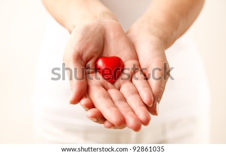 Giving love concept with hands holding a red heart.