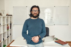 Giving online class. Portrait of young happy bearded male teacher wearing glasses standing against whiteboard and looking at camera. Focus on a man. E-learning. Distance education. Stay home