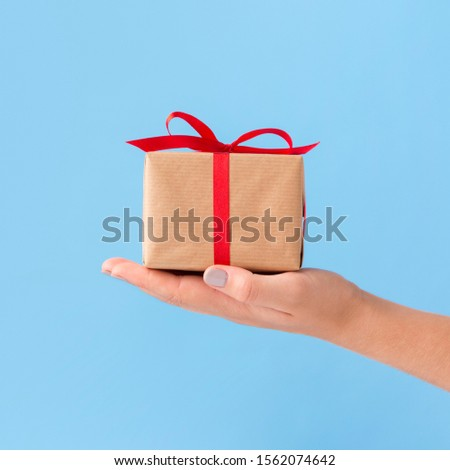 Giving presents. Woman holding Christmas present on blue background