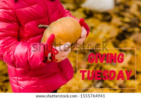 Giving Tuesday. Child's hands with pumpkin and text Giving Tuesday #1555764941