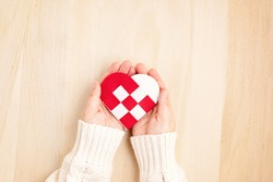 Giving Tuesday concept with woman hands holding red and white heart, charity day concept. Donation, philantropy, help and support idea.  Top view, flat lay
