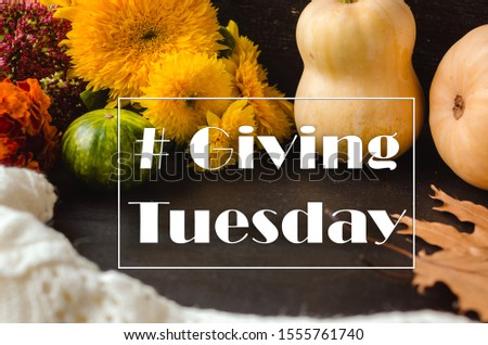 Giving Tuesday. Flat lay with pumpkins, sunflowers and dry leaves on the black background with tag #Giving Tuesday #1555761740