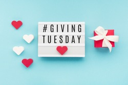 Giving Tuesday, global day of charitable giving after Black Friday shopping day. Charity, give help, donations support concept with text message on lightbox, red hearts  on blue background.