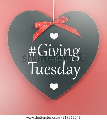 Giving Tuesday message greeting on black heart shape blackboard against a red background, with applied faded filters.  #519263248