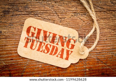 Giving Tuesday sign - a paper price tag with a twine on a rustic wood #1199628628