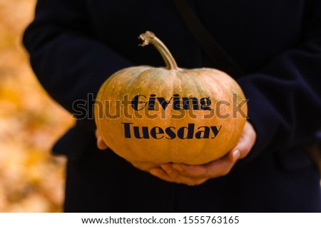 Giving Tuesday. Woman holding the pumpkin with text Giving Tuesday #1555763165