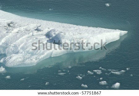Glacial iceberg floating in Glacier Bay, Alaska.  Good details in ice and ripples in water.  Good image for science, weather, or travel.  Conceptual image for climate change or global warming.