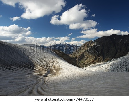 Glacier and clouds. High rocks and snow