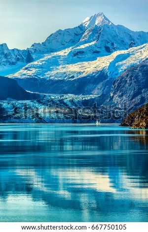 Glacier Bay Alaska cruise vacation travel. Global warming and climate change concept with melting ice. Cruising boat towards landscape of Johns Hopkins Glacier and Mount Fairweather Range mountains. #667750105