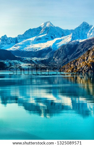 Glacier Bay cruise ship cruising to Johns Hopkins Glacier in Alaska, USA. Summer travel destination for vacation. Mirror water reflection in tranquil arctic sea, famous attraction.