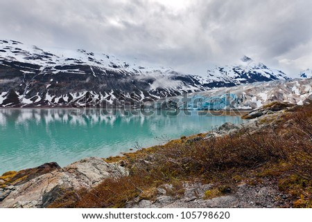 Glacier landscape in Alaska with blue ice reflected in a lake of glacial melt. Glacier Bay wilderness.