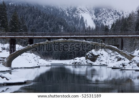 Glacier National Park entrance bridge spanning Flathead River in a winter landscape. Water is reflecting the snow-covered riverbanks and the trees on the mountain in the background. Horizontal shot.